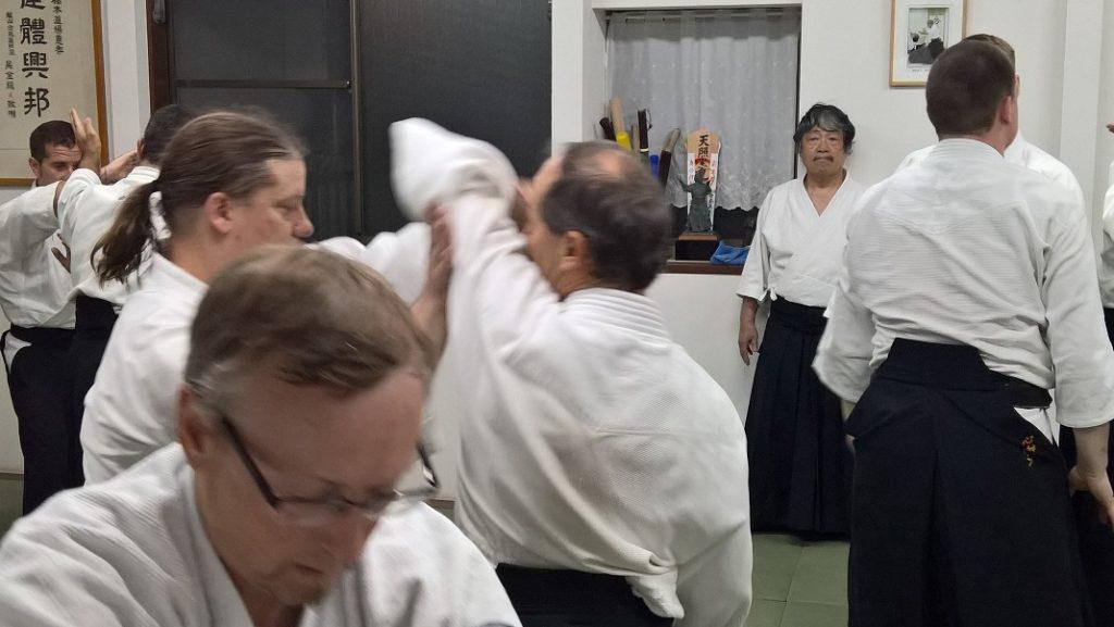 """Siirtyessäsi tatamllle kumalla shomeniin ja tervehdi paikalla olijoita sanomalla """"onegai shimasu!"""", johon muut vastaavat samoilla sanoilla. Sitten treenipuku päälle pukkarissa, jonne myös tavarat jätetään pieniin koreihin. Tuo mukanasi mahdollisimman vähän tavaraa ja jos asut lähistöllä, vaihda treenipuku jo majapaikassa. Normaalien alkukumarrusten jälkeen on vuorossa aikitaiso ja sitten treenataan!"""